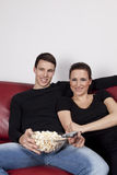 Young Couple with Popcorn Watching TV Royalty Free Stock Images
