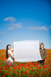 Young couple in the poppy field Stock Photos