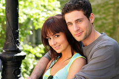Young couple portrait. Portrait of a young man and woman sitting outside on a bench Royalty Free Stock Image