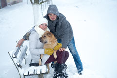 Young couple portrait with dog. A young couple with their dog in the snow Royalty Free Stock Image