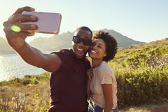 Young Couple Pose For Holiday Selfie On Clifftop Stock Image