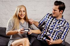 Young man and woman are sitting on the couch and are playing a game Stock Photo