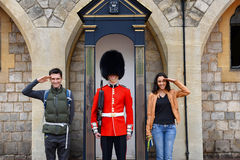 Young couple posing with a beefeater guard. At Windsor Castle, Berkshire, UK smiling and saluting the camera Stock Photos