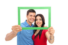 Young couple posing behind a green picture frame Stock Images