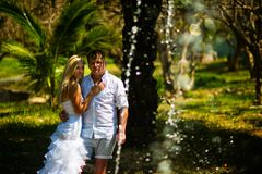 Young couple posing and in the foreground splashing fountain royalty free stock photos