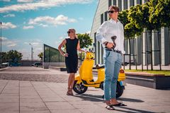 Young couple posing next to a classic Italian scooter at the street stock photography