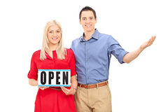 Young couple posing with an open sign Royalty Free Stock Image