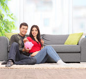Young couple posing with a piggybank at home Royalty Free Stock Image