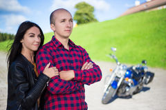 Young couple posing on road with retro motorcycle Stock Photos