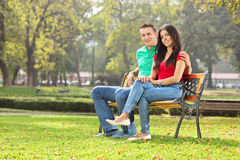 Young couple posing seated on a bench in park Stock Photography