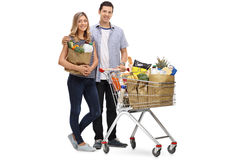Young couple posing with a shopping bag and a cart Stock Image