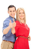 Young couple posing sideways and giving thumbs up Royalty Free Stock Images