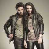 Young couple posing in studio. Dressed in leather jackets, sepia picture Royalty Free Stock Images