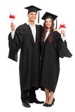 Young couple posing with their diplomas Stock Photography