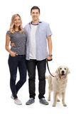Young couple posing with their dog Stock Images