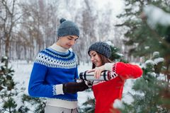 Young couple pouring hot tea out of thermos in winter forest. Happy people relaxing outdoors during holidays royalty free stock photo