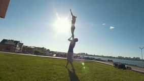Young couple practicing acrobatics performing front bird pose, young man throws a woman in the air balancing on his arms. At sunset, slow motion stock footage