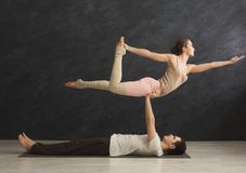 Young couple practicing acroyoga on mat together royalty free stock image
