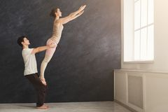Young couple practicing acroyoga on mat together Stock Photography