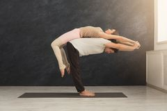 Young couple practicing acroyoga on mat together royalty free stock photo