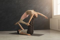 Young couple practicing acroyoga on mat together stock photo