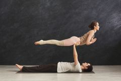 Young couple practicing acroyoga on mat together stock image