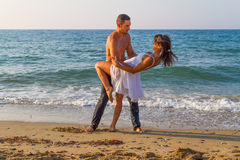 Young couple practicing a dance scene at the beach. Royalty Free Stock Image