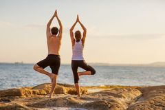 Young couple practicing yoga on the beach at sunset.  stock image