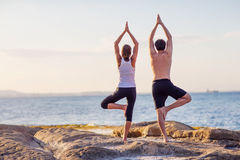 Young couple practicing yoga on the beach Stock Photography