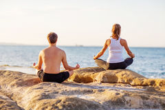 Young couple practicing yoga on the beach Stock Image