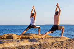 Young couple practicing yoga on the beach at sunset Stock Images