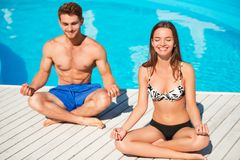 Young couple practicing yoga near swimming pool Stock Photography