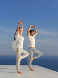 Young couple practicing yoga. At sunset in modern home terace with ocean and sunset in background stock photo