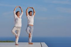 Young couple practicing yoga. At sunset in modern home terace with ocean and sunset in background royalty free stock photo