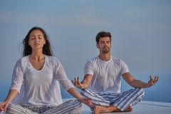 Young couple practicing yoga. At sunset in modern home terace with ocean and sunset in background stock photography