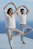 Young couple practicing yoga. At sunset in modern home terace with ocean and sunset in background royalty free stock image