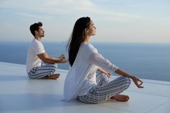 Young couple practicing yoga. At sunset in modern home terace with ocean and sunset in background stock photos