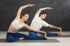 Young couple practicing yoga together in gym. Young couple practicing yoga together. Man and women sitting on mat and doing stretching exercise, copy space stock image
