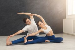 Young couple practicing yoga together in gym stock photo