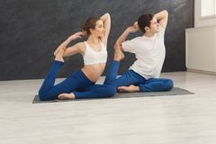 Young couple practicing yoga together in gym royalty free stock photo