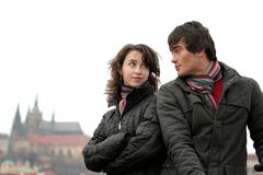 Young Couple in Prague. A young couple - a woman and a man talking intimately; wearing winter jackets; the Prague Castle in the background; sky taken off Stock Photos