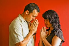 Young Couple Praying. Male and female praying together against a red background Royalty Free Stock Images
