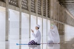Young couple prays to the Allah after doing Salat. Portrait of young couple praying to the Allah after doing Salat in the mosque stock photos