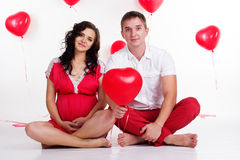 Young couple pregnant mother and happy father. Young attractive couple: pregnant mother and happy father with heart shape balloons isolated on white Stock Image