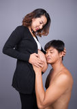 Young couple: pregnant mother and happy father on gray backgroun. Young couple: pregnant mother and happy father on gray wall background Royalty Free Stock Image