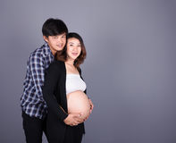 Young couple: pregnant mother and happy father on gray backgroun. Young couple: pregnant mother and happy father on gray wall background Stock Photography