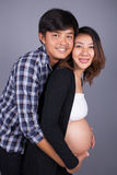 Young couple: pregnant mother and happy father on gray backgroun. Young couple: pregnant mother and happy father on gray wall background Royalty Free Stock Photo