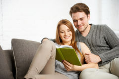 Young couple preparing for examinations. Young students couple preparing for exams on sofa in living room Stock Photo
