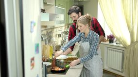 Young couple preparing food. Plate with fried eggs. Breakfast for two stock footage