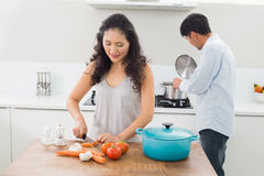 Young couple preparing food together in kitchen Royalty Free Stock Images